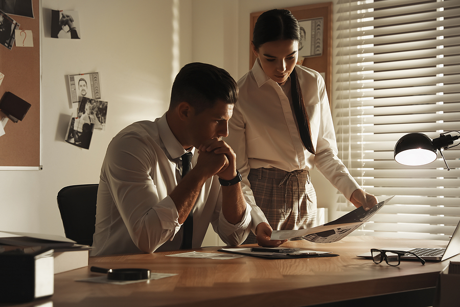 professional detectives working at desk in office