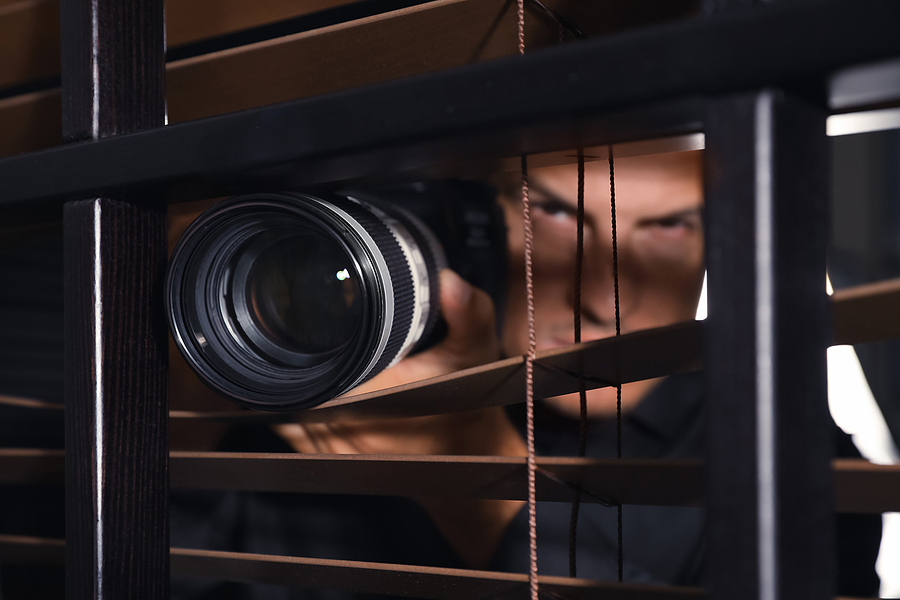 detective with camera spying near window indoors, focus on lens