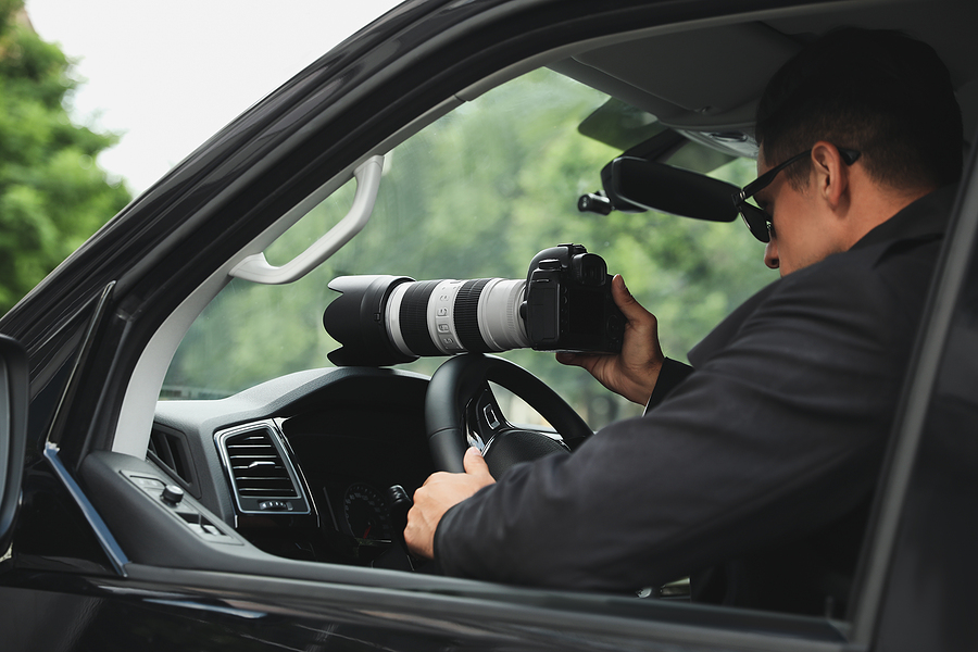 detective with camera spying from car