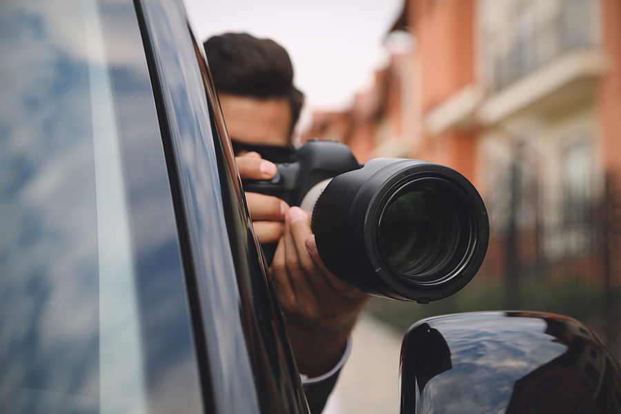 detective with camera spying from car, focus on lens